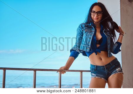 Seductive Sexy Brunette Girl Wearing Short Shorts And Jeans Jacket Posing While Leaning On A Guardra