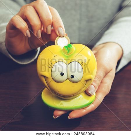 Woman Putting Coins In A Funny Yellow Moneybox, Toned Image. Concept Of Future, Business, Saving Mon