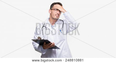 Handsome young doctor man holding a clipboard stressed with hand on head, shocked with shame and surprise face, angry and frustrated. Fear and upset for mistake.