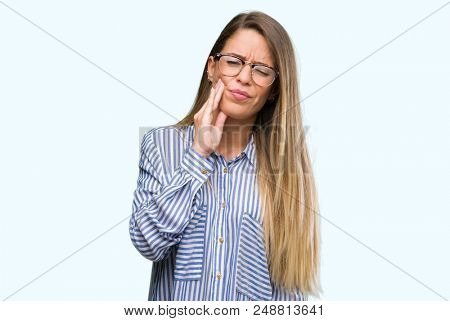 Beautiful young woman wearing elegant shirt and glasses touching mouth with hand with painful expression because of toothache or dental illness on teeth. Dentist concept.