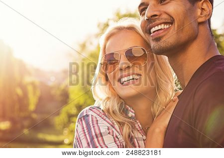 Beautiful young couple hugging and looking away outdoors at sunset. Portrait of happy boyfriend embracing girlfriend with sunglasses at park. Smiling girl hugging guy in love with copy space.
