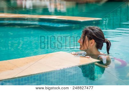 Young Brunette Woman Relaxing In The Swimming Pool In A Resort Hotel