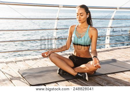 Image of relaxed fcaucasian woman 20s in sportswear sitting on exercise mat in yoga pose and meditating near seaside