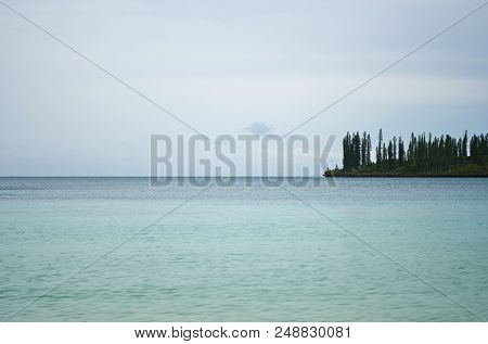 A Headland On The Isle Of Pines Stretches Into The Tranquil Blue Water Of The South Pacific. It Is C