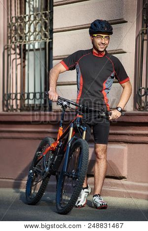 Young Male Biker In Cycling Clothes And Protective Helmet Standing Near Old Historical Building Next