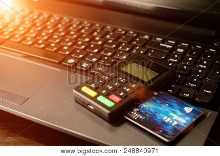 Bank Card And Payment Device Lying On Keyboard In Rays Of The Sun. Concept Of Internet Crime, Hackin