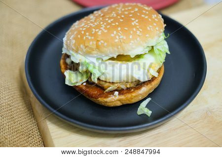 Tasty Burger With Pork And Fried Egg On Black Dish
