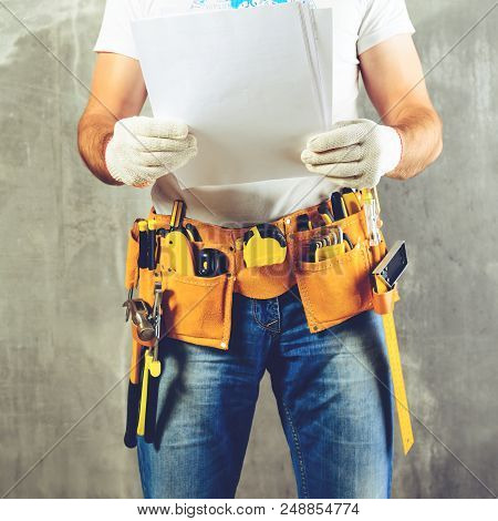 Unidentified Handyman With Hand On Waist And Tool Belt With Construction Tools Holding The Project P