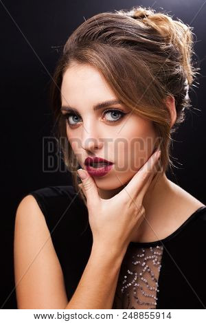 pretty young model with fresh professional elegant makeup and a coiffure made by stylists in a beauty salon touching her face by a hand poster