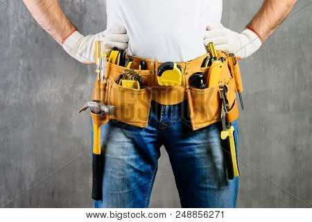 Unidentified Handyman With Hands On Waist And Tool Belt With Construction Tools Against Grey Backgro