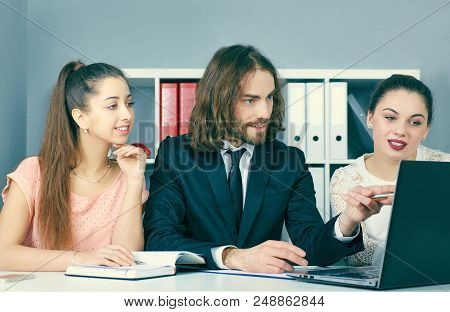 Three Young Coworkers Working Together In A Modern Coworking Studio. Business Partners Using Laptop