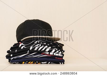 Pile Of Brand New T-shirts, Dark Tones, With Print And A Black Straight Flap Cap Over The Pile