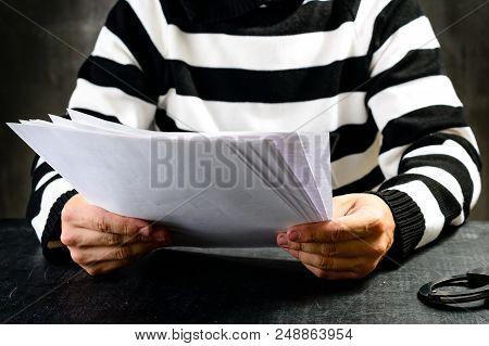 Unidentified Prisoner In Prison Stripped Uniform Sitting On The Chair In The Dark Interrogation Room