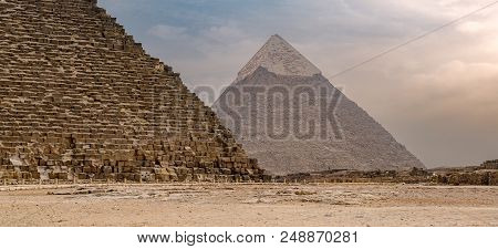 Cropped Great Pyramid Of Khufu And Pyramid Of Khafre In The Far Distance With Cloudy Sky Background