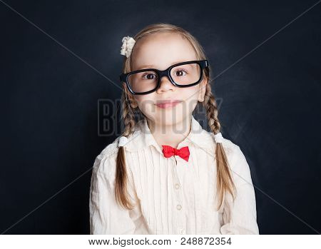 Smart Child Girl Smiling On Blue Blackboard Background. Back To School And Education Concept. Intell