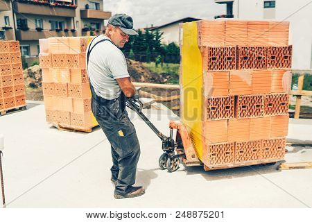 Industrial Worker On Construction Site, Moving Bricks And Working On Building Walls