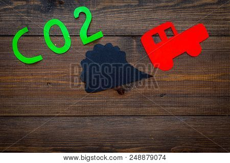 Car exhaust, co2, smoke. Car and smoke cutout on dark wooden background top view poster