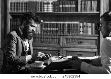 Man In Suit Or Journalist With Friend In Library. Journalism Concept. Man With Beard Interviews Writ