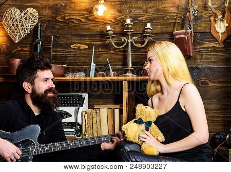 Man Play Guitar While Lady Holds Teddy Bear In Hands. Couple Spend Romantic Evening, Wooden Interior