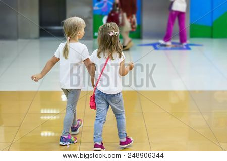 Two Cute Blond Little Girls Walking Together In Mall. Pair Of Kid Friends Holding Hands During Walk.