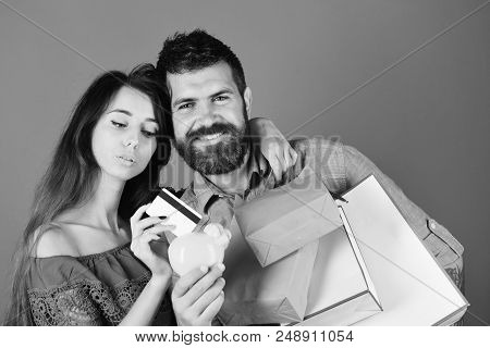 Guy With Beard And Girl With Smiling Faces Do Shopping. Couple In Love Holds Shopping Bags On Blue B