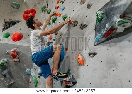 Boulderer Climbing Up A Bouldering Wall. Male Climber Making His Way Up An Artificial Climbing Wall