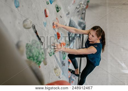 High Angle View Of A Boulderer Climbing Up A Bouldering Wall. Female Climber Making Her Way Up An Ar