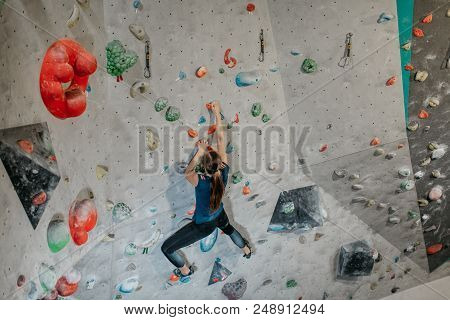 Back View Of A Boulderer Climbing Up A Bouldering Wall. Female Climber Making Her Way Up An Artifici