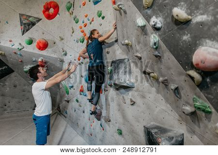 Man And Woman Climbing In An Indoor Bouldering Gym. Bouldering Instructor Spotting Whilst A Female B