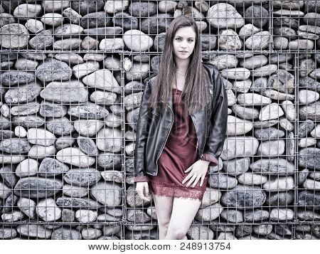 Young Woman In Modern City Setting, Wearing Minidress And Black Leather Jacket