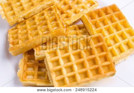 Close-up Of Homemade Fresh Brown Waffles. View To Stacked Wafles On A White Plate. Bakery And Food B