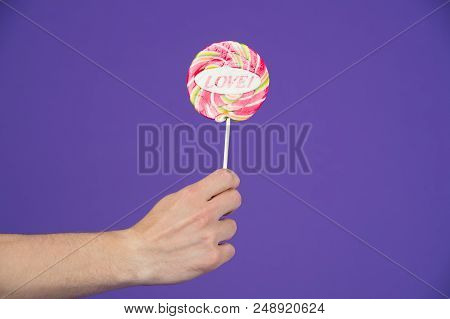 Sweet Feelings. Lollipop With Word Love. Male Hand Holds Lollipop With Inscription Love. Romantic Gi
