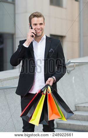 Businessman Shopping. Man Carries Shopping Bags While Have Phone Conversation Urban Background. Succ
