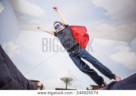 Boy super hero wearing cape and mask using imagination to fly, motion blur on boy