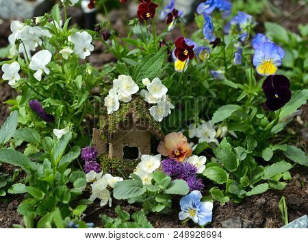 Small fairy house in viola flowerbed. Lovely miniature house for greeting cards, wedding or birthday concept, real estate, downsizing, home ownership. Vintage summer background poster