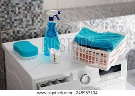 part of washing machine and blue laundry powder for washing day