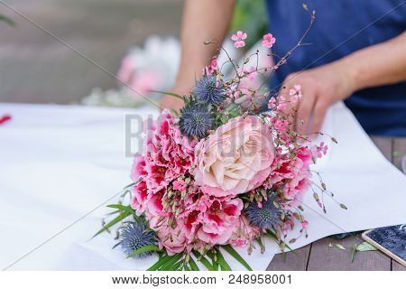 Male Florist Creating Beautiful Bouquet In Flower Shop. Outdoor Working In Flower Shop. Man Assistan