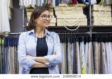 Portrait Of Happy Mature Woman Owner With Crossed Arms In Interior Fabrics Store, Background Fabric