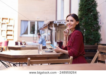Summer Terrace. Dark-haired Woman Feeling Very Relaxed While Sitting On Summer Terrace Of The Restau