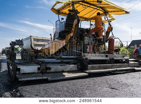 Worker Operating Asphalt Paver Machine During Road Construction And Repairing Works. A Paver Finishe