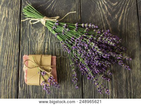 Handmade Soap Wrapped In Paper, Near On Gray Surface Bunch Of Lavender
