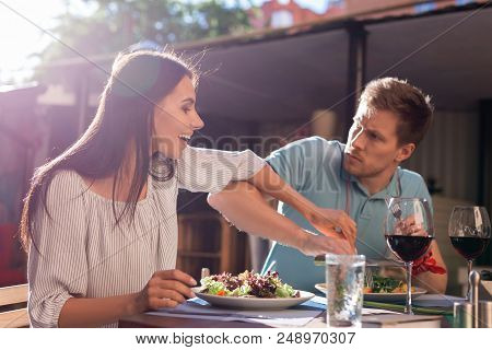 Greedy Man. Greedy Angry Man Feeling Furious While Not Letting His Woman Trying His Salad
