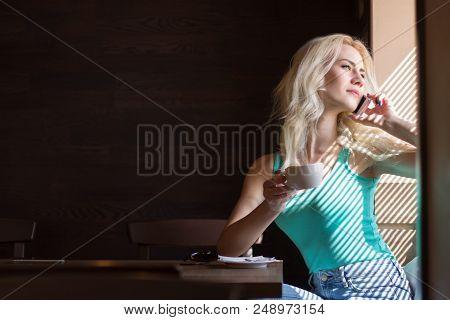 Woman Drinks Coffee Near The Window With Jalousie. Copy Space