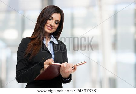 Portrait of a beautiful woman taking notes on a notebook