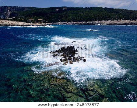Aerial above waves crashing over rugged rocky coastline
