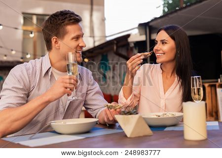 With Wife. Handsome Mature Man Wearing Stylish Striped Shirt Having Champagne And Eating Oysters Wit