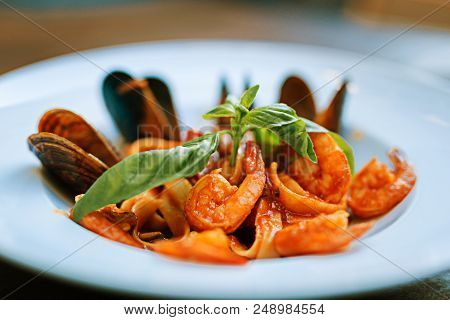 Portion of seafood. Nice portion of delicious yummy seafood in tomato sauce standing on the table poster