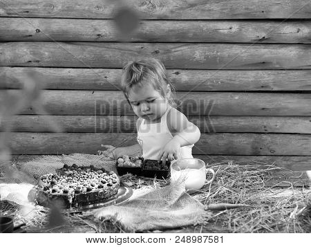 Cute Little Boy In White Pinafore Eats Berries Raspberry Gooseberry At Rustic Table With Fruit Cake
