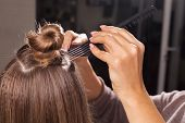 professional hairdresser making a coiffure with a bun to a young woman using different brushes in a beauty salon. concept of carefull hair treating poster