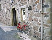 a red bicycle is resting against the abbey in iona, scottland. poster